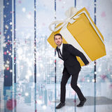 Composite image of stylish man with giant gift Stock Photos