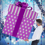 Composite image of stylish man with giant gift Royalty Free Stock Image