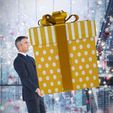 Composite image of stylish man with giant gift Stock Images