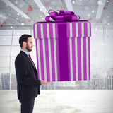 Composite image of stylish man with giant gift Royalty Free Stock Images