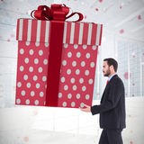 Composite image of stylish man with giant gift Royalty Free Stock Photography