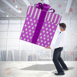 Composite image of stylish man with giant gift Royalty Free Stock Photo