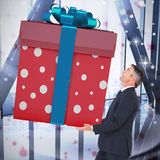 Composite image of stylish man with giant gift Stock Photography