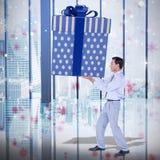Composite image of stylish man with giant gift Stock Image