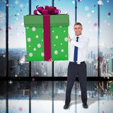 Composite image of stylish man with giant gift Royalty Free Stock Photos