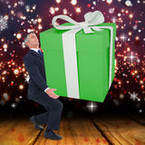 Composite image of stylish man with giant gift Stock Image