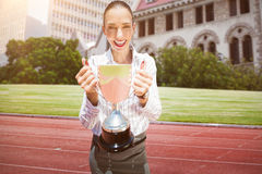 Composite image of successful businesswoman holding a trophy. Successful businesswoman holding a trophy against running track in front of city stock illustration