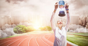 Composite image of successful businesswoman lifting a trophy. Successful businesswoman lifting a trophy against composite image of racetrack in city royalty free stock photos