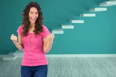 Composite image of successful cute brunette posing. Successful cute brunette posing against steps in a blue room Royalty Free Stock Photos
