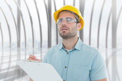 Composite image of supervisor looking away while writing on clipboard. Supervisor looking away while writing on clipboard against white room with large window Royalty Free Stock Images