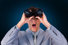 Composite image of suprised businessman looking through binoculars Royalty Free Stock Photo