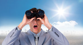 Composite image of suprised businessman looking through binoculars Royalty Free Stock Photography
