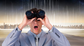 Composite image of suprised businessman looking through binoculars Stock Photography