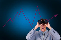 Composite image of suprised businessman looking through binoculars Royalty Free Stock Image