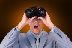 Composite image of suprised businessman looking through binoculars Stock Photo