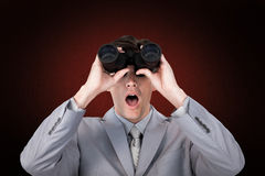 Composite image of suprised businessman looking through binoculars Stock Image