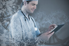 Composite image of surgeon using digital tablet. Surgeon using digital tablet  against red dna pattern on screen Stock Images