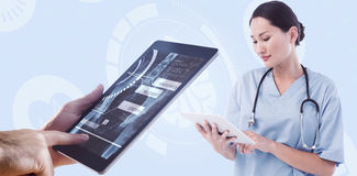 Composite image of surgeon using digital tablet with group around table in hospital Stock Photo