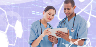Composite image of surgeons looking at digital tablet in hospital. Surgeons looking at digital tablet in hospital against medical icons Royalty Free Stock Photo