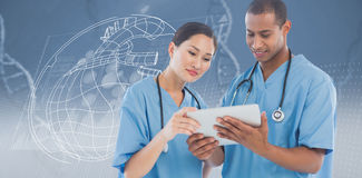 Composite image of surgeons looking at digital tablet in hospital. Surgeons looking at digital tablet in hospital against view of dna Stock Photo