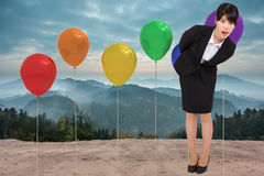 Composite image of surpised businesswoman bending Royalty Free Stock Photo