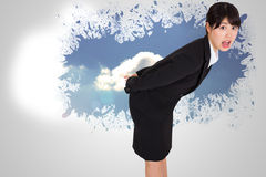 Composite image of surpised businesswoman bending Stock Image