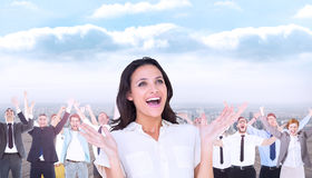 Composite image of surprised brunette with hands up Stock Photography