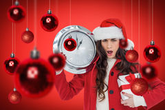 Composite image of surprised brunette holding a clock and gift Stock Photo