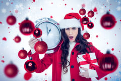 Composite image of surprised brunette holding a clock and gift Stock Image