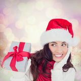Composite image of surprised brunette in santa hat holding gift Royalty Free Stock Photos