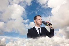 Composite image of surprised businessman standing and holding binoculars. Surprised businessman standing and holding binoculars  against blue sky with white Royalty Free Stock Images