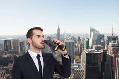 Composite image of surprised businessman standing and holding binoculars Royalty Free Stock Image