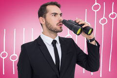 Composite image of surprised businessman standing and holding binoculars Royalty Free Stock Photos
