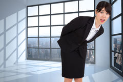 Composite image of surprised businesswoman bending Royalty Free Stock Image