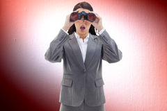 Composite image of surprised businesswoman looking through binoculars Royalty Free Stock Photo
