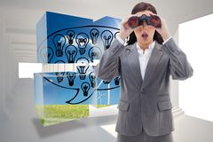 Composite image of surprised businesswoman looking through binoculars Royalty Free Stock Image