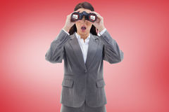 Composite image of surprised businesswoman looking through binoculars Stock Photos