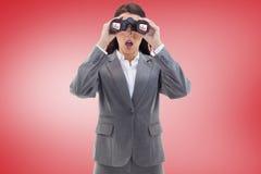 Composite image of surprised businesswoman looking through binoculars Stock Photos