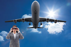 Composite image of surprised businesswoman looking through binoculars Royalty Free Stock Photography