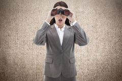 Composite image of surprised businesswoman looking through binoculars Stock Photo