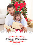 Composite image of surprised father and his girl opening christmas gifts Royalty Free Stock Photography