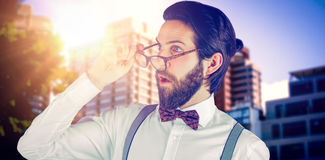 Composite image of surprised man holding eyeglasses while looking away Royalty Free Stock Images