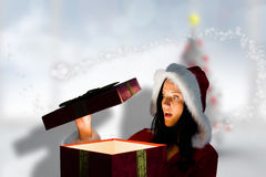 Composite image of surprised woman opening christmas present Stock Images