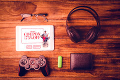 Composite image of tablet and glasses next to joystick music headphone and wallet Royalty Free Stock Image