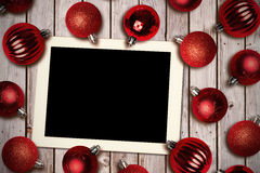 Composite image of tablet pc. Tablet pc against christmas baubles Royalty Free Stock Photography