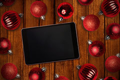 Composite image of tablet pc. Tablet pc against christmas baubles Royalty Free Stock Images