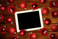 Composite image of tablet pc. Tablet pc against christmas baubles Stock Images