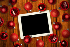 Composite image of tablet pc. Tablet pc against christmas baubles Stock Photography