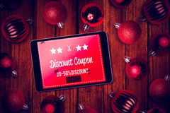 Composite image of tablet pc. Tablet pc against christmas baubles Royalty Free Stock Image
