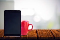 Composite image of tablet pc. Tablet pc against steaming cup of coffee Stock Images